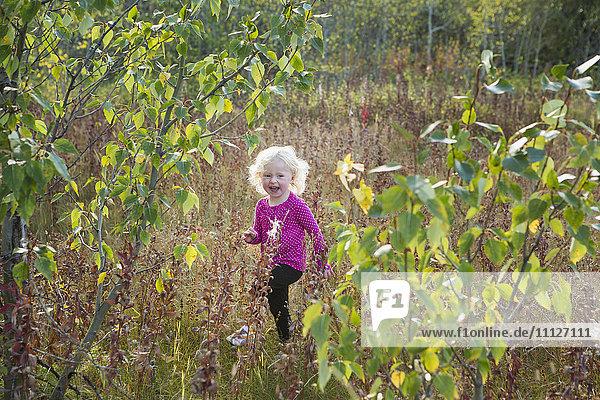 Caucasian girl walking in rural meadow