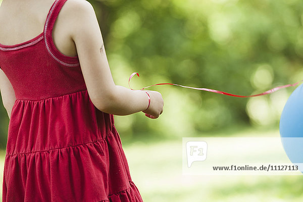 Girl with balloon tied to wrist outdoors