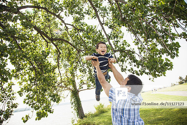 Japanese father playing with son in park