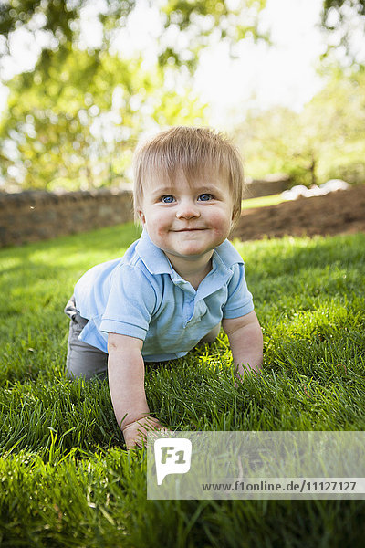 Smiling boy crawling on grass
