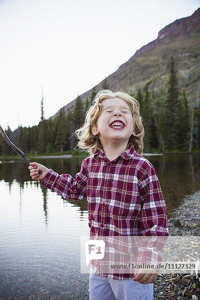 Boy making a face by still rural lake