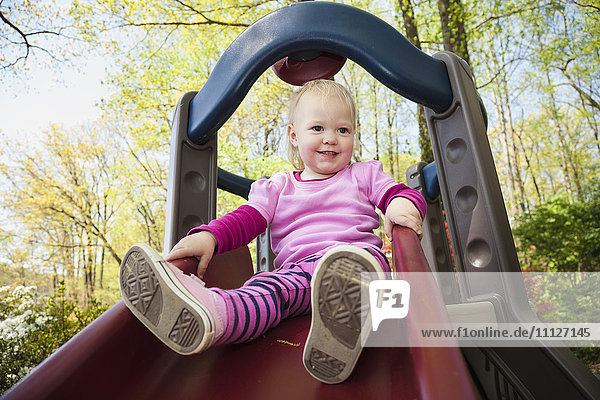 Caucasian girl playing on slide outdoors