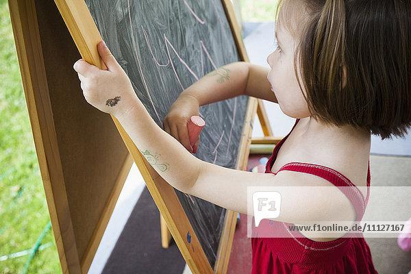 Girl drawing on blackboard easel