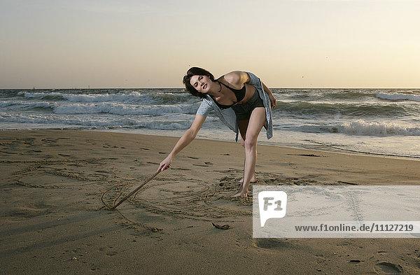 Caucasian woman drawing on beach sand