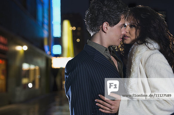 Elegant couple kissing on urban street at night