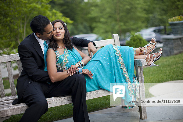 Indian man kissing wife in traditional clothing