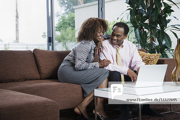 African woman watching husband type on laptop in living room