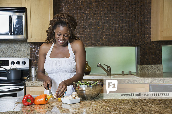 African woman fixing healthy meal in modern kitchen