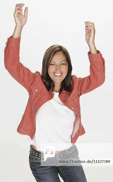 Portrait of Hispanic woman smiling with arms raised
