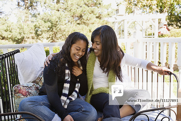 Hispanic teenager and woman laughing on porch
