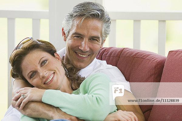 Caucasian couple hugging on porch
