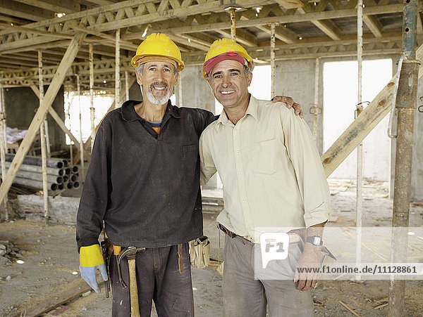 Hispanic workers hugging at construction site