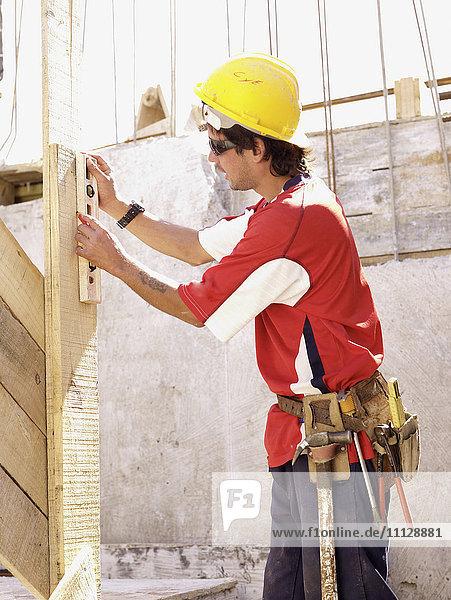 Hispanic worker using level on construction site