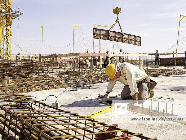 Hispanic worker kneeling at construction site