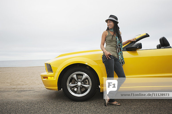 Chinese woman standing near convertible at beach