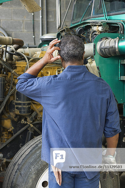 African mechanic in repair shop scratching head