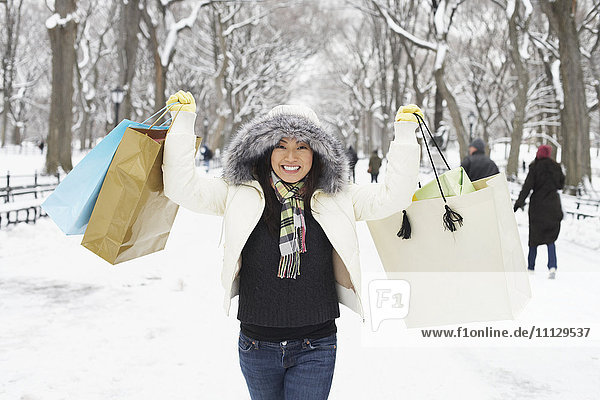 Korean woman in snowy park carrying shopping bags