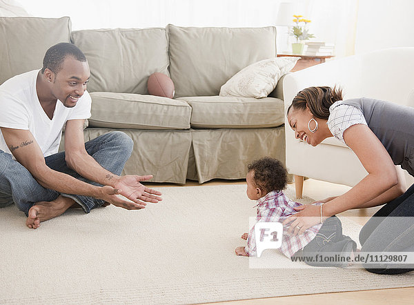 African couple with baby in living room