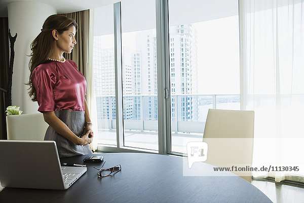 Hispanic woman standing next to laptop and looking out window