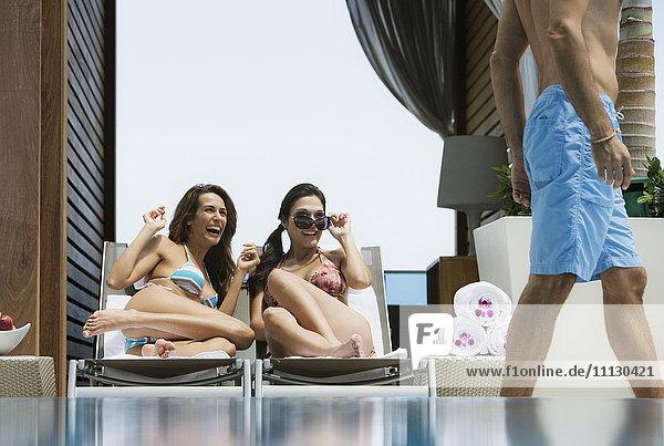 Hispanic women in bikinis eyeing passing man