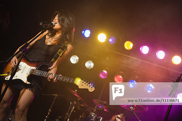 Asian woman singing and playing electric guitar onstage