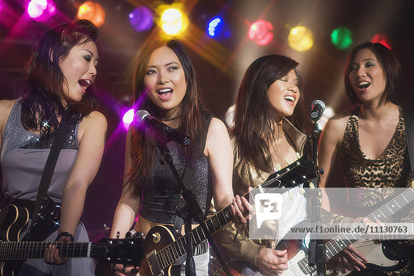 Asian women singing and playing electric guitar onstage