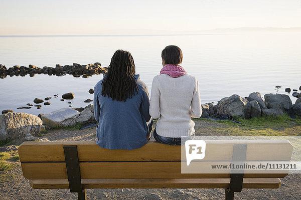 Black couple sitting on bench near shore