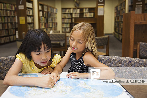 Girls looking at atlas in library