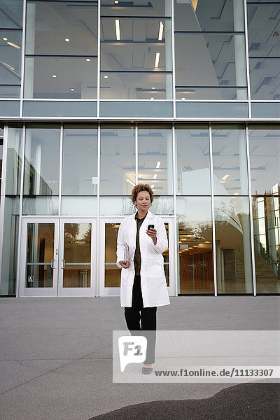 Doctor walking and text messaging on cell phone