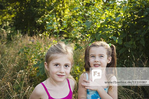 Caucasian girls standing in woods
