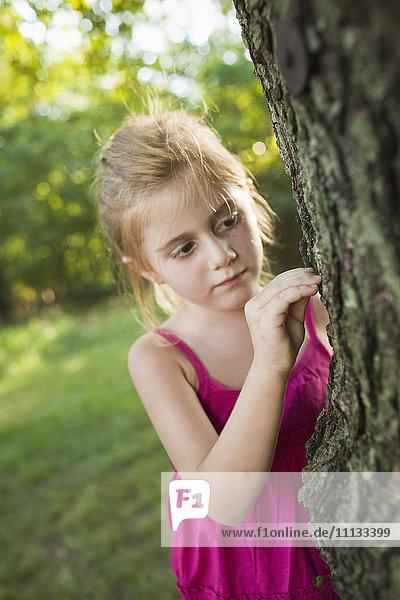 Caucasian girl looking at tree