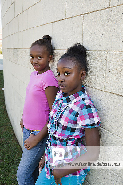 Black girls leaning against wall
