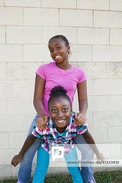 Black girl giving friend a piggyback ride
