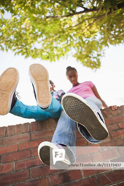 Black girls sitting on wall