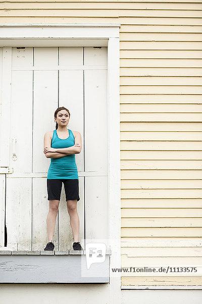 Asian woman in sportswear standing on loading dock