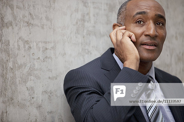 Mixed race businessman talking on cell phone