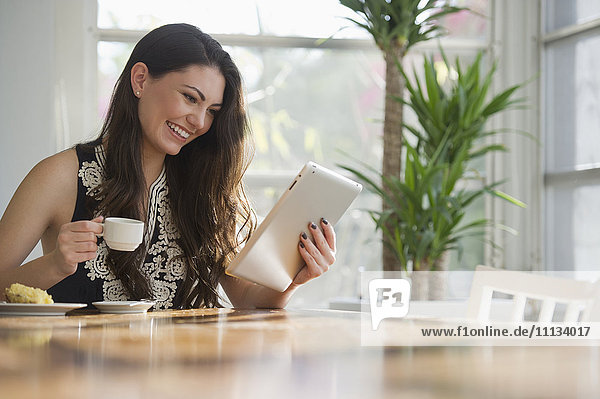 Hispanic woman drinking coffee and using digital tablet