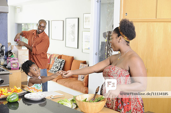 Black girl helping mother prepare food in kitchen