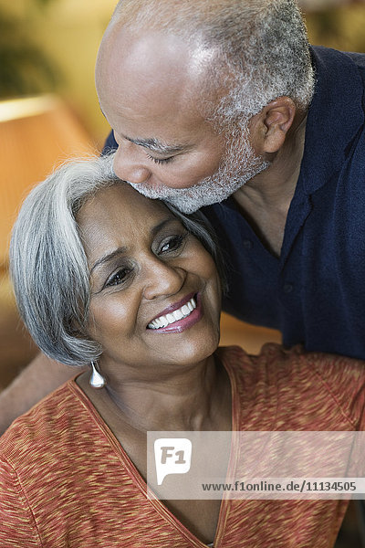African American man kissing wife's forehead