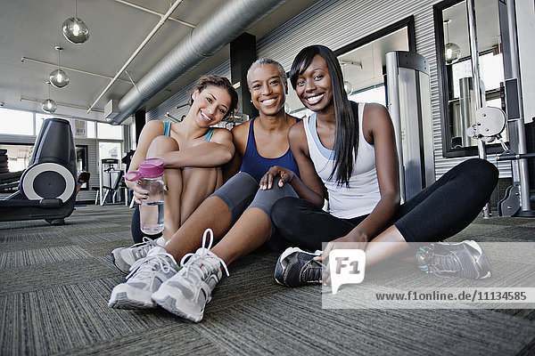 Smiling woman sitting on health club floor together