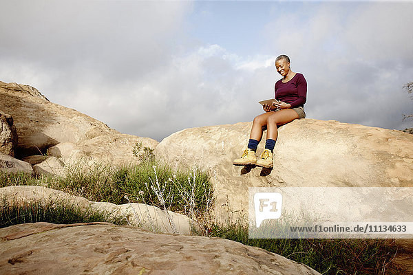 Black woman using digital tablet on rock