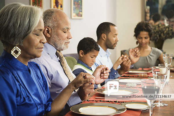African American family saying grace at dining table