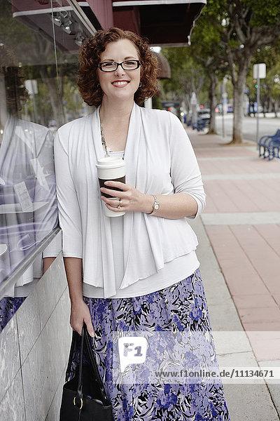 Mixed race woman drinking coffee on sidewalk
