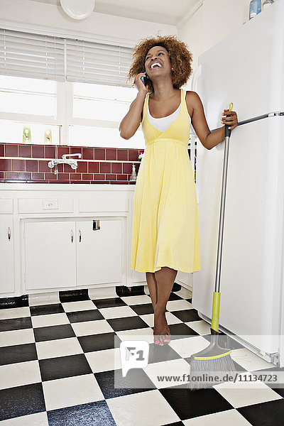 African American woman talking on cell phone in kitchen