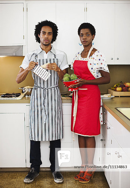 African American woman and husband cooking in kitchen