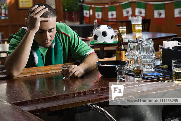 Unhappy man drinking in sports bar
