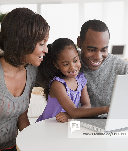 African American family using laptop together