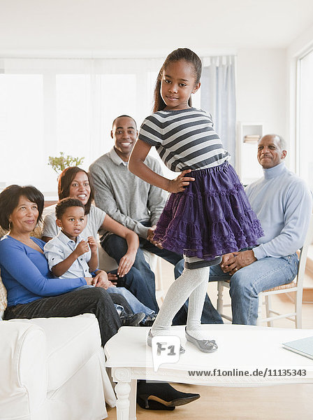 African American family watching daughter standing on table