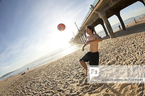 Hispanic man playing with soccer ball on beach