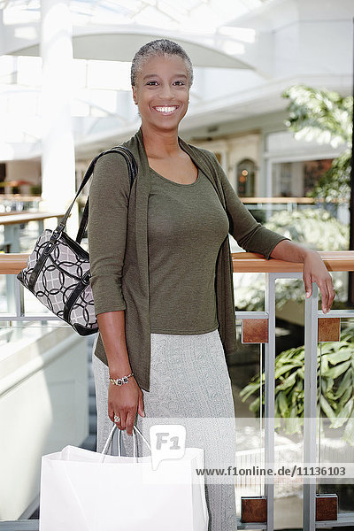 Black woman holding shopping bags in mall